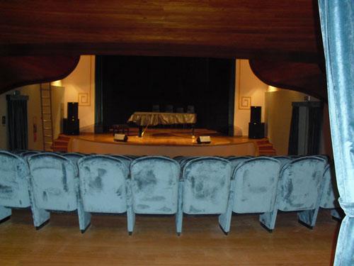 Immagine dell'ingresso alla platea del Teatro Verdi con gli schienali delle poltronicine e sullo sfondo il palco